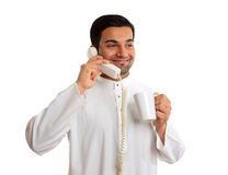 Traditional ethnic businessman on phone. An arab business man dressed in traditional white  robe, eg kameez, thobe, kurta, etc.  He is holding a coffee whilst Royalty Free Stock Photography