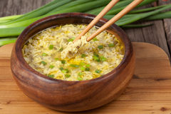 Traditional ethnic egg drop soup restaraunt recipe. With food sticks holding pieces of eggs in wooden bowl stock photos