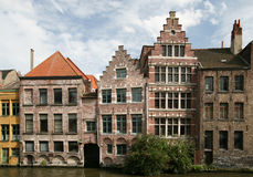 Traditional European architecture. Uneven traditional European brick houses on the bank of the canal stock photography