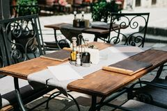 Traditional European cafe. On the table are the menu and there are sauces or butter. There are chairs nearby. Waiting royalty free stock photo