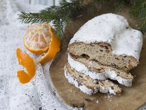 Traditional European Christmas pastry, fragrant home baked stollen, with spices and dried fruit. Sliced on wooden table royalty free stock photography