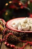 Traditional European Christmas pastry vanillekipferl. Homemade half moon cookies in icing sugar on red plate decorated with fir royalty free stock image