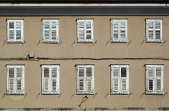 Traditional european wooden shutters on a brown facade of an old residential building Royalty Free Stock Photo