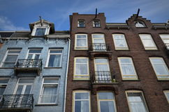 Traditional Facades in Amsterdam, the Netherlands. View of a blue and a brown facade of traditional buildings in Amsterdam Royalty Free Stock Images