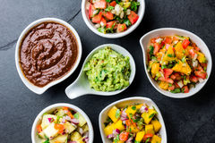 Traditional famous mexican sauces chocolate chili mole poblano, pico de gallo, avocado guacamole, salsa bandera, pinapple salsa, m. Ango salsa on slate gray stock photo