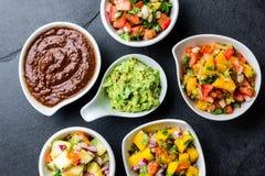 Traditional famous mexican sauces chocolate chili mole poblano, pico de gallo, avocado guacamole, salsa bandera, pinapple salsa, m stock photo