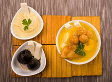 Traditional fanesca serving sitting on wooden surface with accessories next to it such as molo mashed potatoes and fig Stock Photo