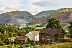 Traditional Farmhouse and Lakeland fells. A traditional whitewashed Farmhouse with associated stone built barns, set in a wooded landscape against a picturesque Stock Photos