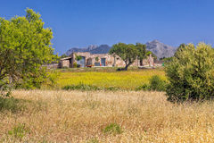 Traditional Farmhouse Near Pollensa, Mallorca. A scenic view of a traditional Mallorcan farmhouse near Pollensa with the Victoria Peninsula in the background Stock Images