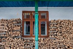 Traditional farmhouse wall decorated with firewood, green pillar and clothesline stock images