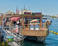 Traditional fast food bobbing boat serving fish sandwiches at Eminonu with chefs preparing meals, Istanbul, Turkey. Istanbul, Turkey - April 25, 2017 Royalty Free Stock Photo