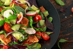 Traditional fattoush salad on a plate with pita croutons, cucumber, tomato, red onion, vegetables mix and herbs royalty free stock images