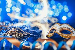 Traditional female carnival venetian mask on bokeh background. Masquerade, Venice, Mardi Gras, Brazil concept. Traditional female carnival venetian mask on blue stock images