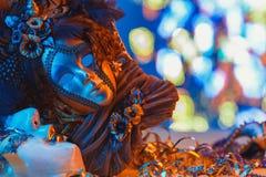 Traditional female carnival venetian mask on bokeh background. Masquerade, Venice, Mardi Gras, Brazil concept. Traditional female carnival venetian mask on blue stock photography
