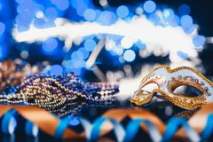 Traditional female carnival venetian mask on bokeh background. Masquerade, Venice, Mardi Gras, Brazil concept. Traditional female carnival venetian mask on blue royalty free stock photo