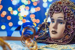 Traditional female carnival venetian mask on bokeh background. Masquerade, Venice, Mardi Gras, Brazil concept. Traditional female carnival venetian mask on blue royalty free stock photography