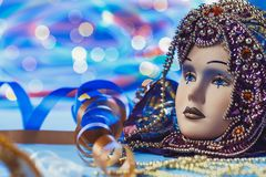 Traditional female carnival venetian mask on bokeh background. Masquerade, Venice, Mardi Gras, Brazil concept. Traditional female carnival venetian mask on blue royalty free stock images