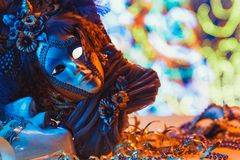 Traditional female carnival venetian mask on bokeh background. Masquerade, Venice, Mardi Gras, Brazil concept. Traditional female carnival venetian mask on blue royalty free stock photos