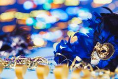 Traditional female carnival venetian mask on bokeh background. Masquerade, Venice, Mardi Gras, Brazil concept. Traditional female carnival venetian mask on blue stock photos