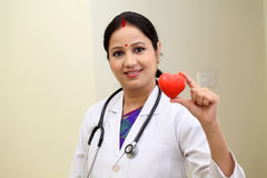 Traditional female doctor holding red heart shape stock images
