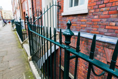 Traditional fence in front of city houses in London Royalty Free Stock Photo