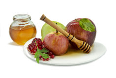 Traditional festive food for Rosh Hashanah,  on wh. Apples, honey and pomegranate are traditional sweet food for Jewish holiday Rosh Hashanah Royalty Free Stock Image