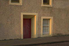 Traditional Fife door. Picturesque fisherman's cottage in the village of Pittenweem in the East Neuk of Fife, Scotland, UK, Europe with red door below street Stock Photography