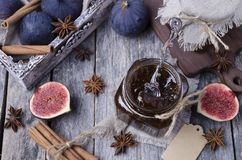 Traditional Fig jam. With spices in glass on wooden background. Selective focus stock photos