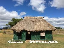 Traditional Fijian Bure. This is a traditional Fijian Bure with thatched roof made from dried leaves with tropical weather climate of warm blue sky Stock Photo