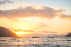 Traditional filipino boats floating in the warm sunset light, El Nido, Philippines. Traditional filipino boats in calm waters at sunset with pink fluffy clouds Royalty Free Stock Photo