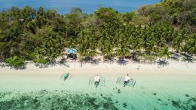 Traditional filipino boats located in a tropical beach with palm trees and white sand in a sunny day. Travel destination in The. Awesome aerial view of isolated stock photos