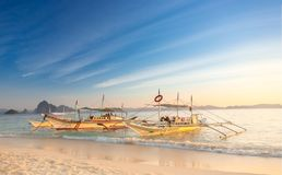 Traditional filipino boats on white sandy beach at sunset in Port Barton, Palawan Island, Philippines. Traditional filipino boats in calm sea at sunset in Port Stock Photography