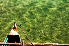 Traditional filipino fishing boat. An old Filipino fishing boat floating on the clear sea water Royalty Free Stock Photo