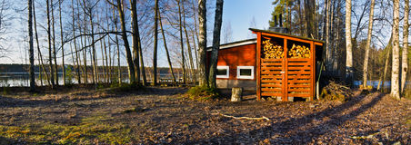 Traditional Finish Sauna in the border of lake. Traditional Finish Sauna colored in red is in the border of lake in the forest. This typical wooden construction Royalty Free Stock Photography