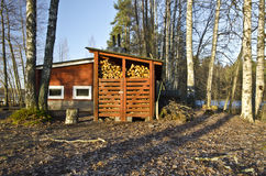 Traditional Finish Sauna. Colored in red is in the border of lake in the forest. This typical wooden construction in Finland has a dry firewood storage place royalty free stock photos