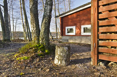 Traditional Finish Sauna in the Nature. Traditional Finish Sauna colored in red is in the border of lake in the forest. This typical wooden construction in Royalty Free Stock Images