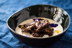 Traditional Finnish Easter rye pudding, with cream. Decorated with edible flowers Royalty Free Stock Photo