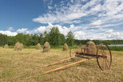 Traditional Finnish haystacks and hayrake Royalty Free Stock Image