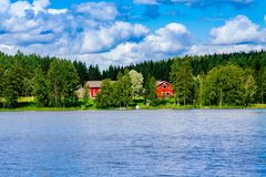 A traditional Finnish wooden cottage with a sauna and a barn on the lake shore. Summer rural Finland. Royalty Free Stock Images
