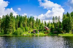A traditional Finnish wooden cottage with a sauna and a barn on the lake shore. Summer rural Finland. Royalty Free Stock Image