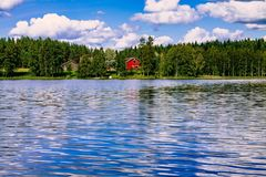 A traditional Finnish wooden cottage with a sauna and a barn on the lake shore. Summer rural Finland. Stock Photography
