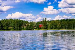 A traditional Finnish wooden cottage with a sauna and a barn on the lake shore. Summer rural Finland. Stock Photos