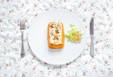 Traditional fish cake. Hake cake with tomato, shrimps, chive and salad cream on Flower table cloth. Top view. Stock Photo