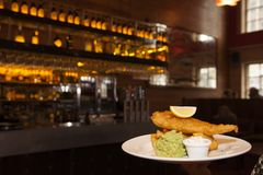 Traditional Fish and Chips at restaurant. Traditional dish of Fish and Chips on a white plate with a lemon slice and sides, in a cosy restaurant with warm stock photography