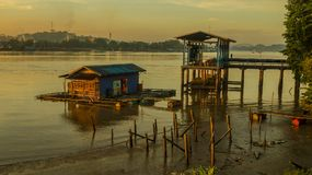Traditional fish culture on Mahakam river, Borneo, Indonesia. Wooden house with fish net beneath the surface at dawn Stock Images
