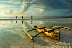 Traditional fisher boat in Zanzibar with people going to fish on. Low tide Stock Photos