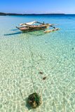 Traditional fisherman boat lying near the beach in clear water Stock Photos