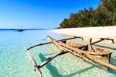 Traditional fisherman boat lying near the beach in clear water Stock Photo