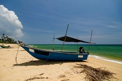 traditional fisherman boat moored over beautiful sea view and sandy beach under bright sunny day Royalty Free Stock Images