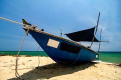 traditional fisherman boat moored over beautiful sea view and sandy beach under bright sunny day Royalty Free Stock Photography